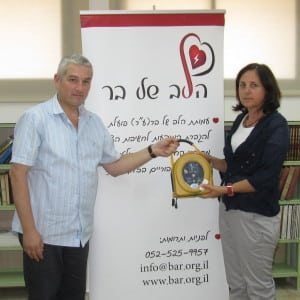 Eyal Greenbaum, CEO Sha'ag Medical Group, presents a HeartSine AED to Mrs. Tamar Vayintraub, Manager of Hativat Levona School