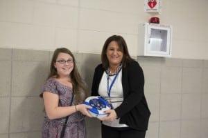 Brooke Conlon presents HeartSine AED to Principal Kathy Perry