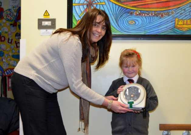 Model Primary School Principal Joanne Lyons and pupil Jenny Craig, receiving a HeartSine defibrillator donated to the school by Jenny's parents. Photo courtesy of the Carrick Times